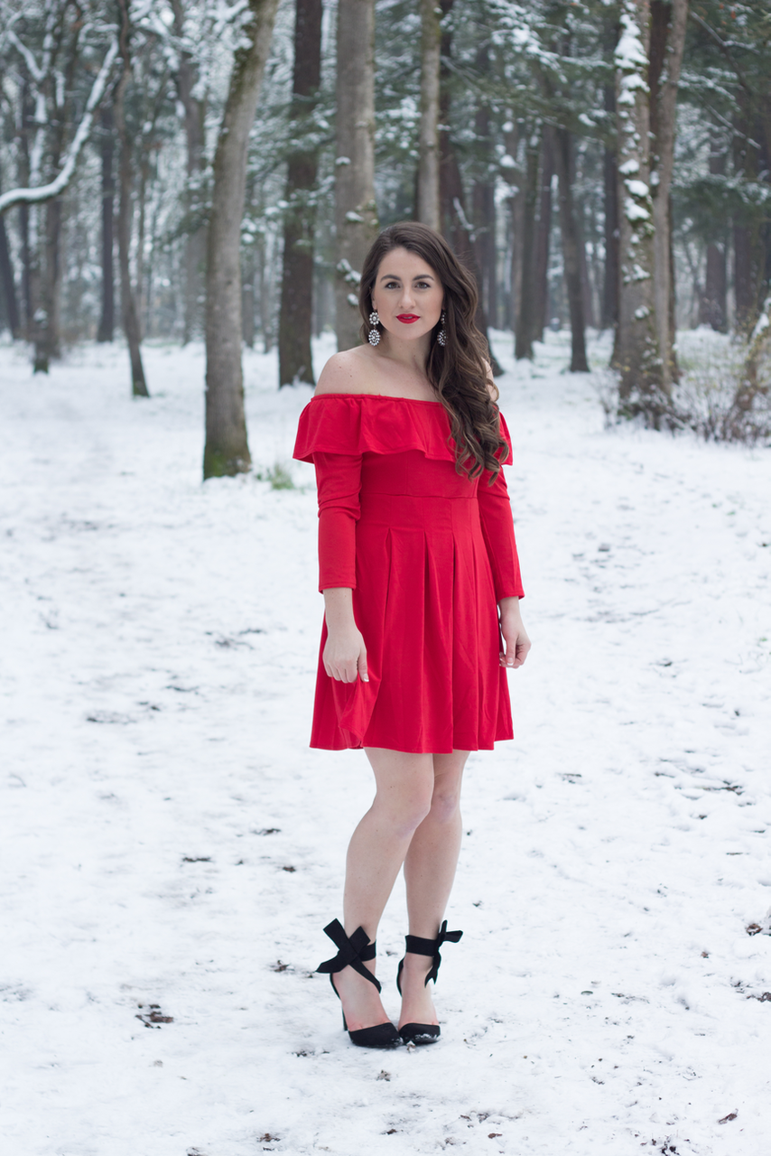 A classic Winter look in a black pea coat, bow heels, and a red off the shoulder dress in the snow.