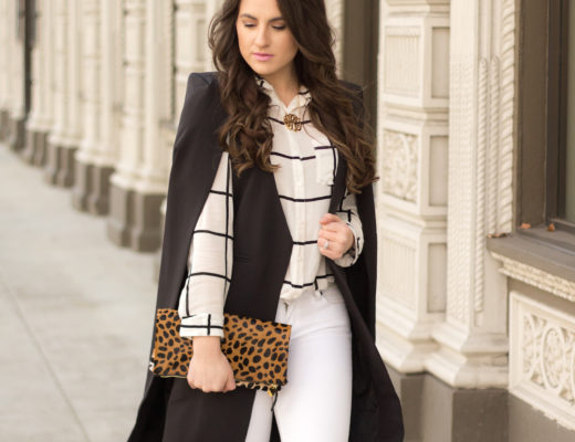 Strolling in a new black cape layered over a windowpane blouse and distressed jeans.