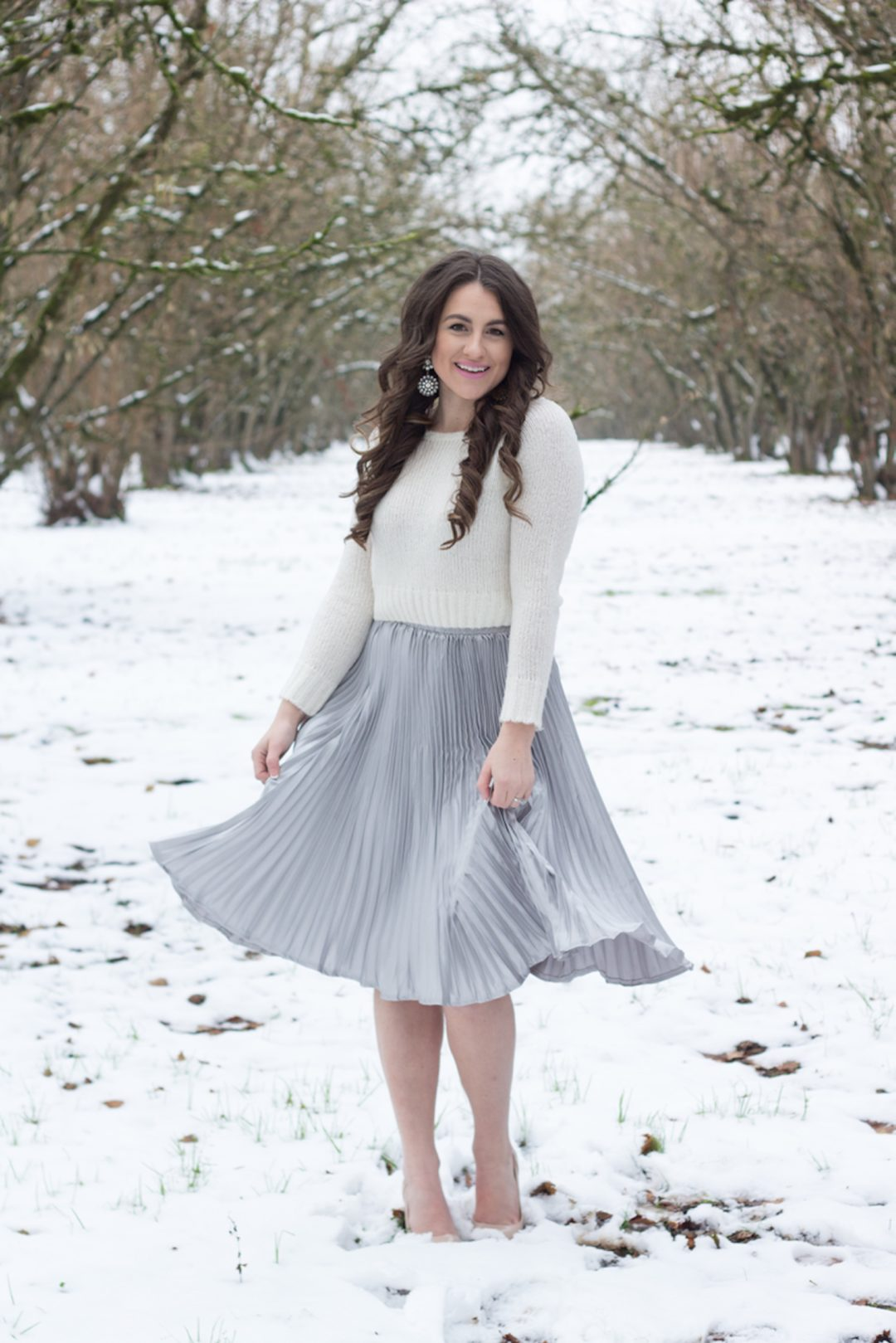 Celebrating the new year with One Hope champagne in a silver pleated skirt and cream sweater while walking in the snow.